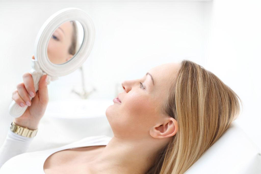 Kobieta po zabiegu kosmetycznym przegląda się w lusterku